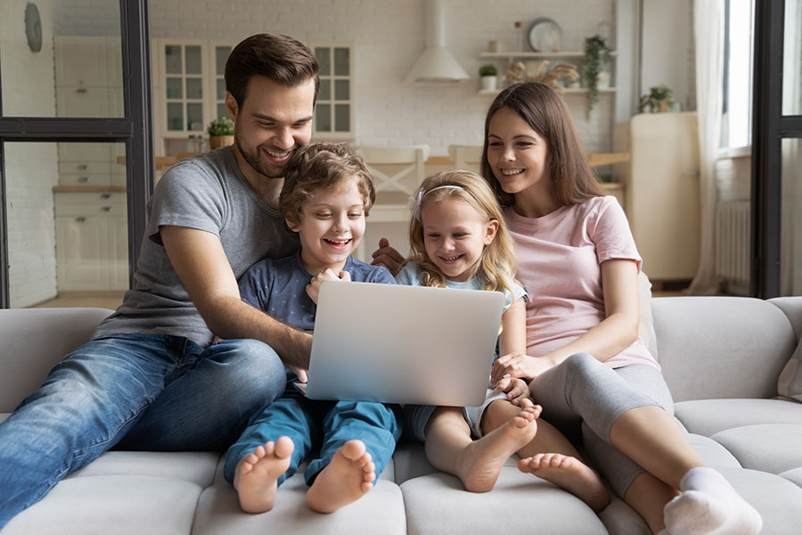 Client Center - Portrait of Happy Family Sitting on the Sofa Using a Laptop