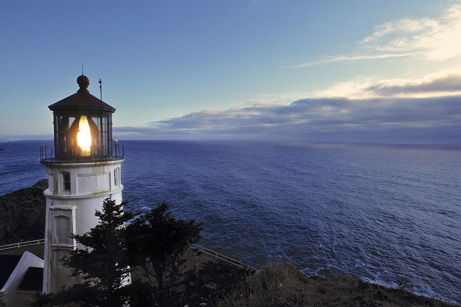 Contact - View of Lighthouse Shining Light in the Evening on the Coast